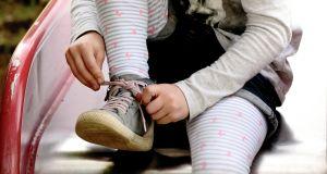 Mädchen auf Rutsche bindet sich die Schuhe