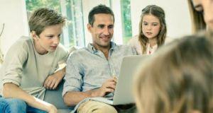Familie schaut gemeinsam auf Noteook