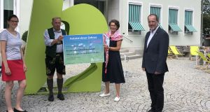 Vier Personen mit einem Spendenscheck für die Hochwasseropfer in Bad Münstereifel vor dem Holzkirchner Rathaus