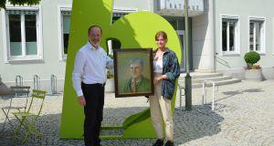 Bürgermeister Schmid und Lea Wagner mit dem Gemälde von Olaf von Löwis vor dem Rathaus
