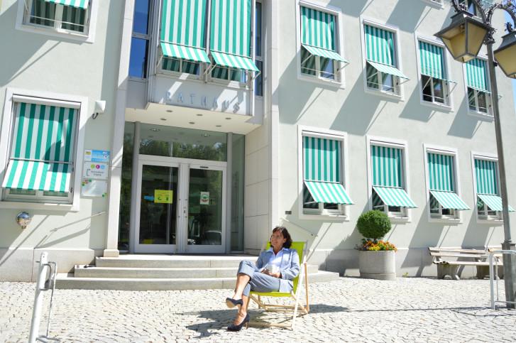 Liegestuhl und Frau vor dem Rathaus