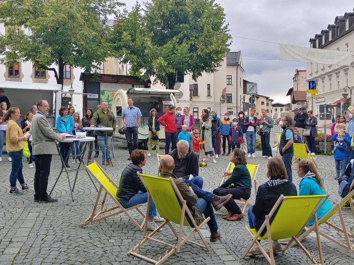 Bürgermeister spricht vor vielen Leuten auf dem Marktplatz